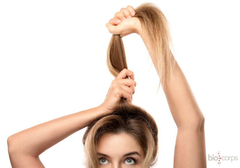 Mulher levando o cabelo para cima em rabo de cavalo