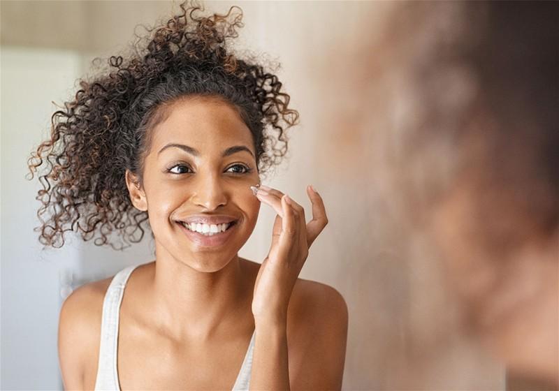 mulher passando produto no rosto